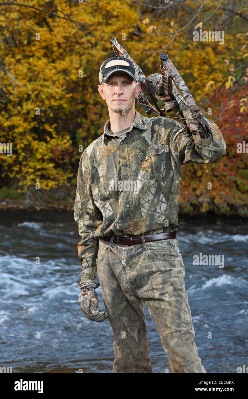 handsome bow hunter by a fall stream - Stock Image
