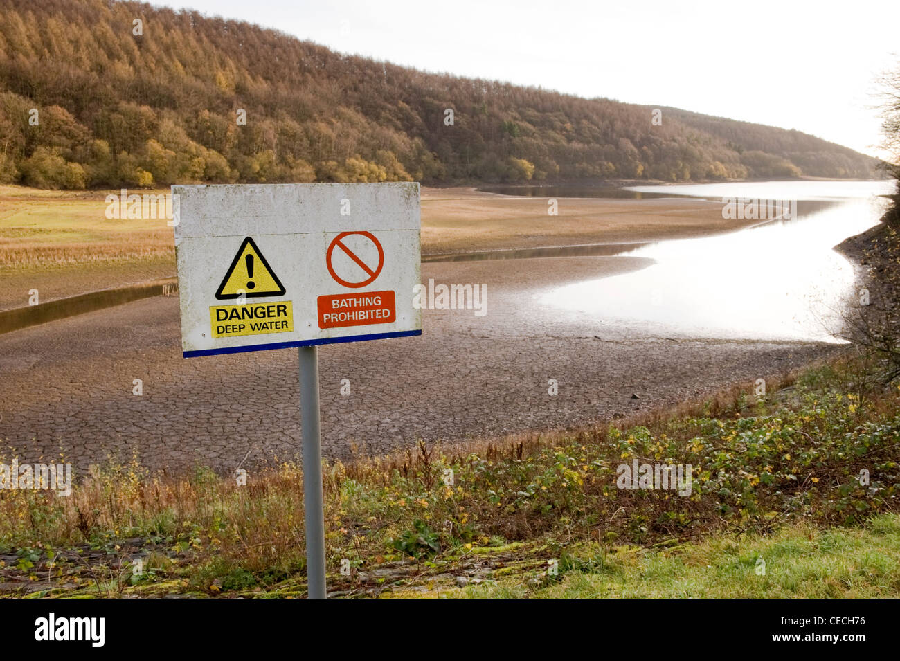 Lindley Wood Reservoir showing very low water levels and two danger signs. - Stock Image