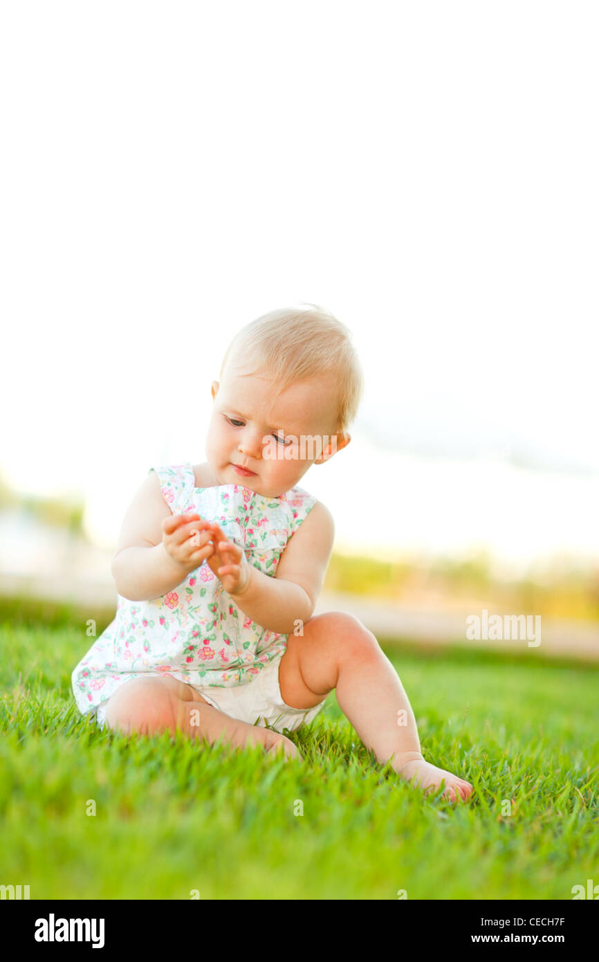 Baby playing on grass - Stock Image