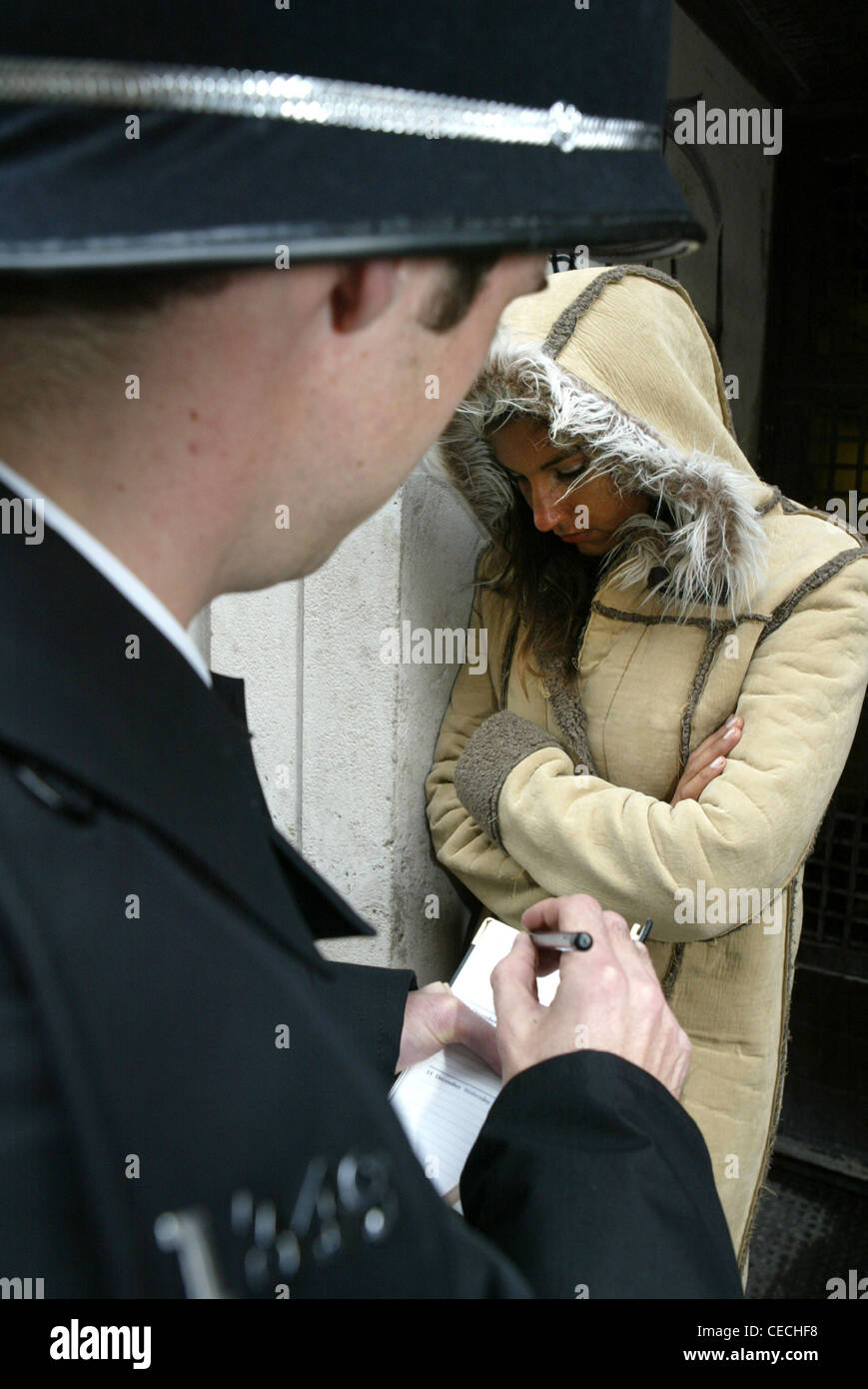 Policeman stops and questions a youth on the streets of London, UK - Stock Image