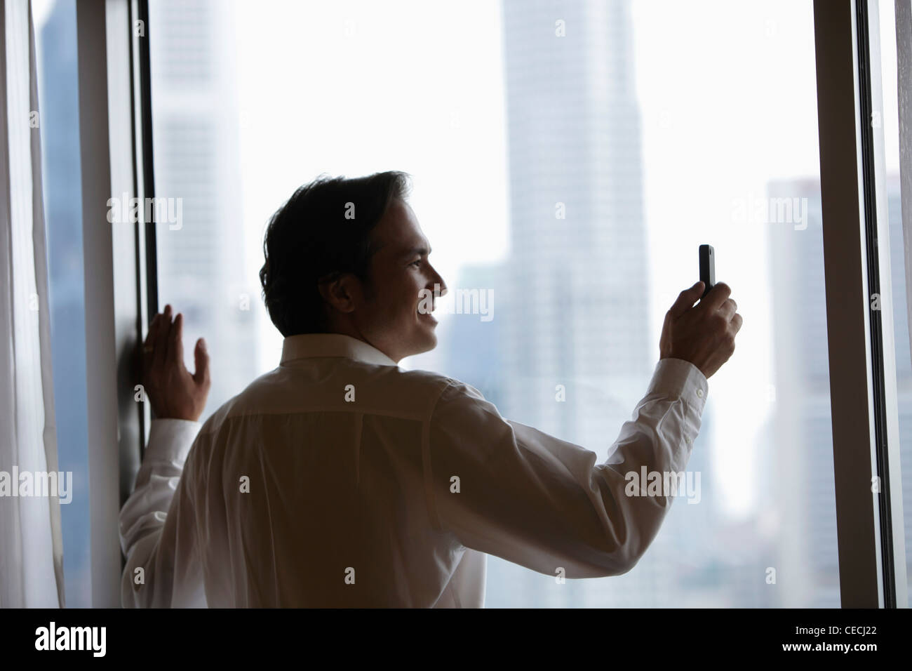 profile of businessman taking a photo with phone - Stock Image
