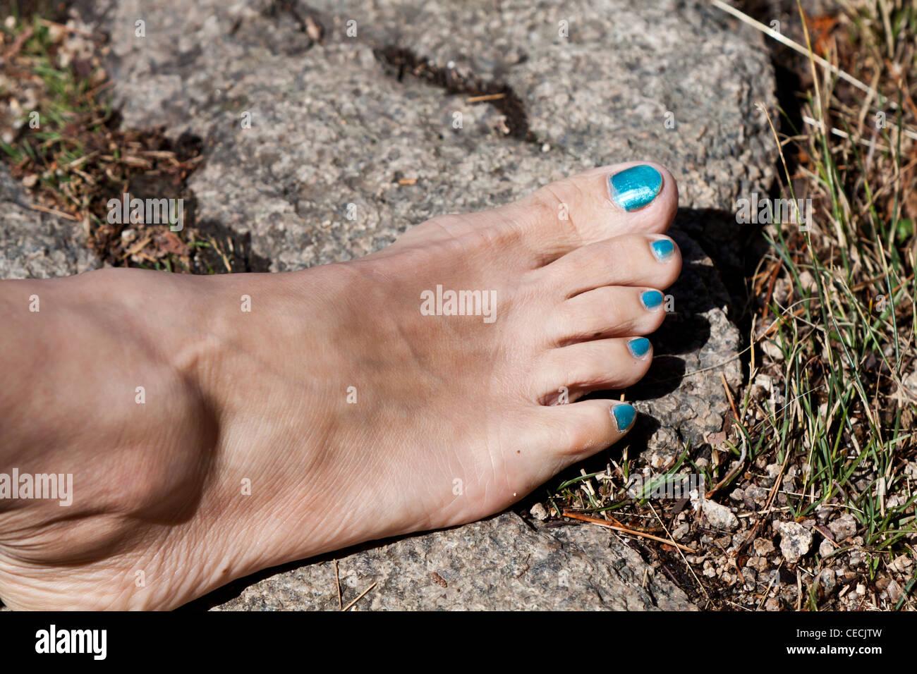 Turquoise polished toe nails - Stock Image