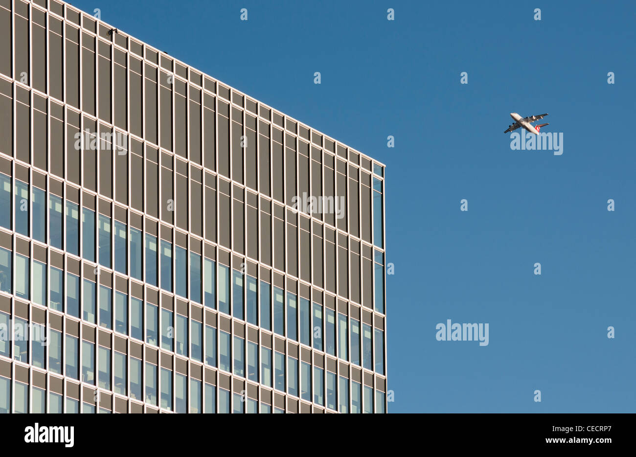 BAe Avro RJ100 Airliner and State Street Bank at 20 Churchill Place , Canary Wharf, Docklands, London, United Kingdom - Stock Image