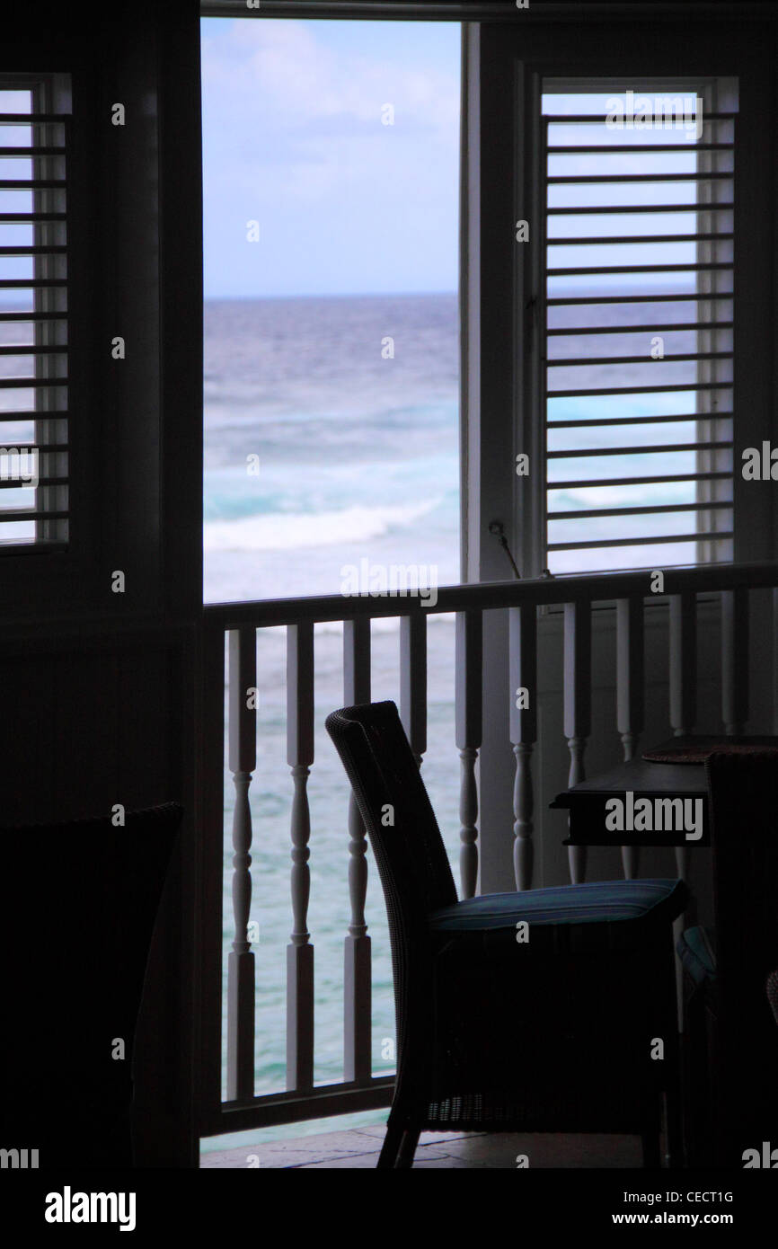 A chair beside a window looking out onto the Atlantic Ocean on the east side of Barbados, West Indies - Stock Image