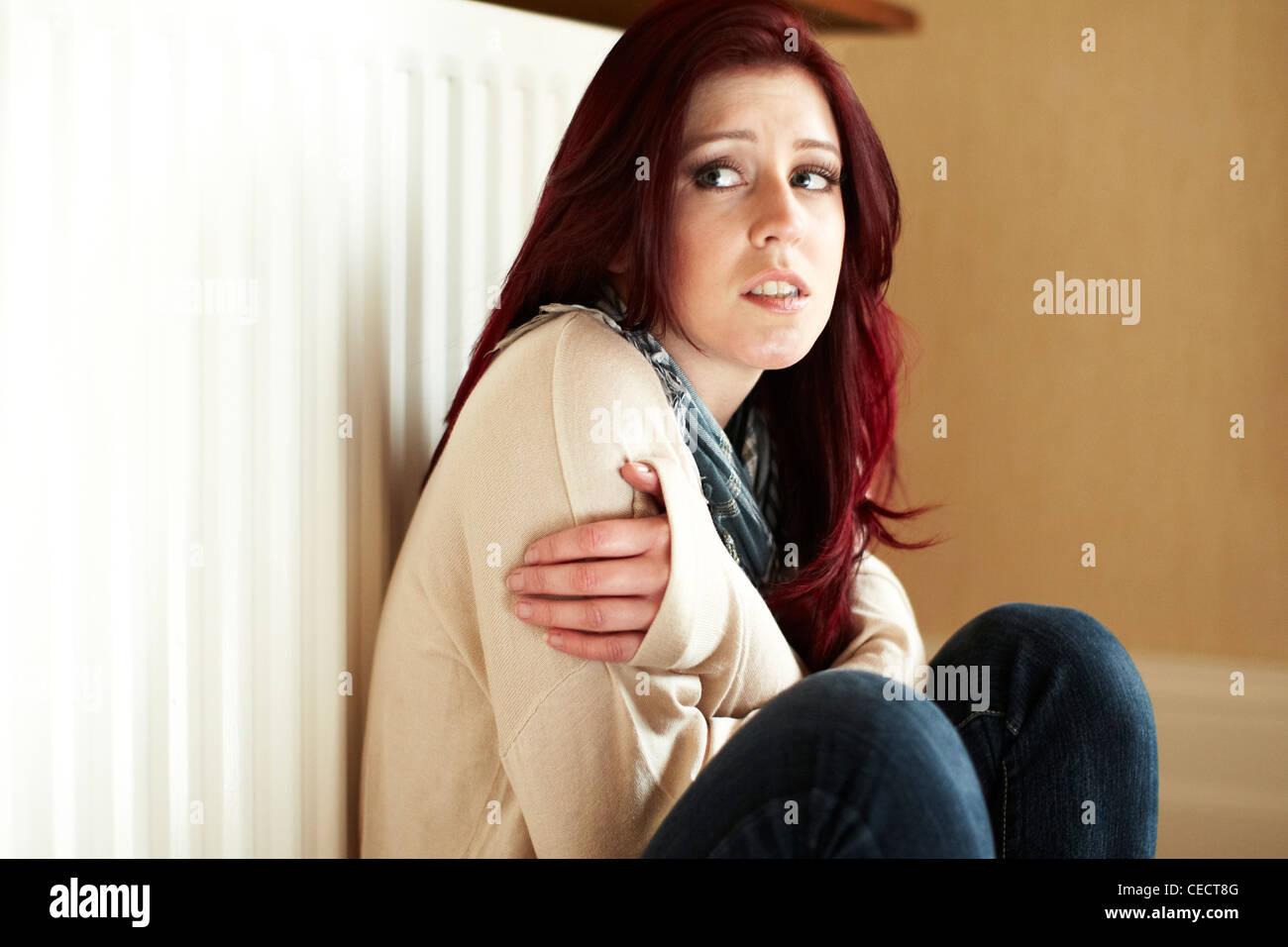 Cold girl next to radiator - Stock Image