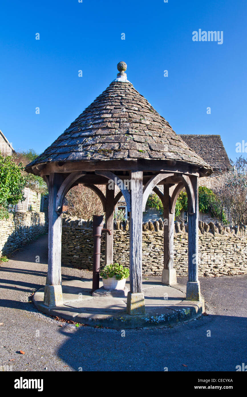 The old village water pump is the quaint English village emblem of Biddestone, Wiltshire, UK - Stock Image