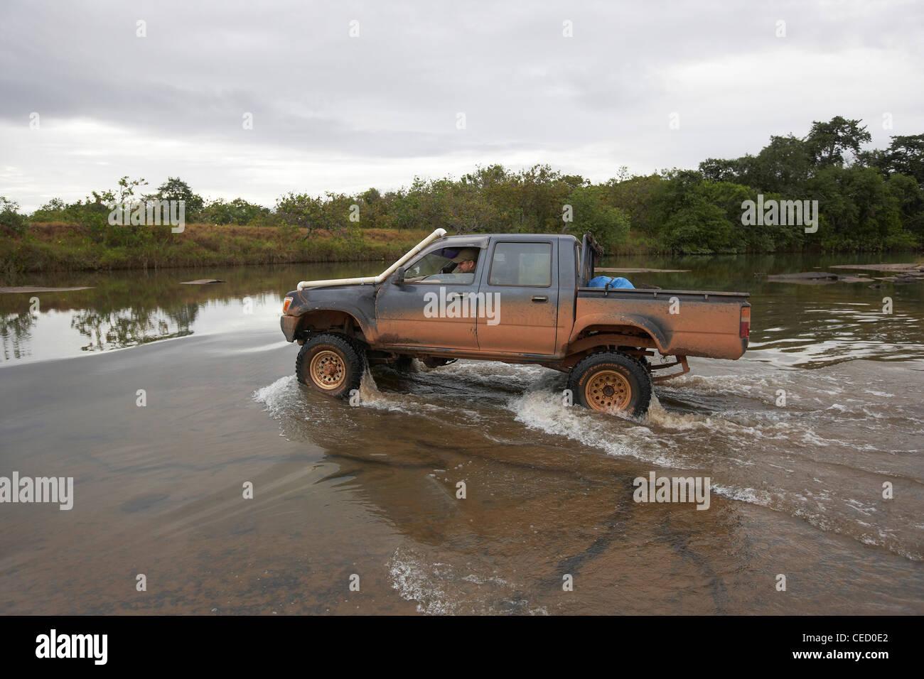 4x4 vehicle fording a river in the Rupununi Savannah, Guyana. - Stock Image