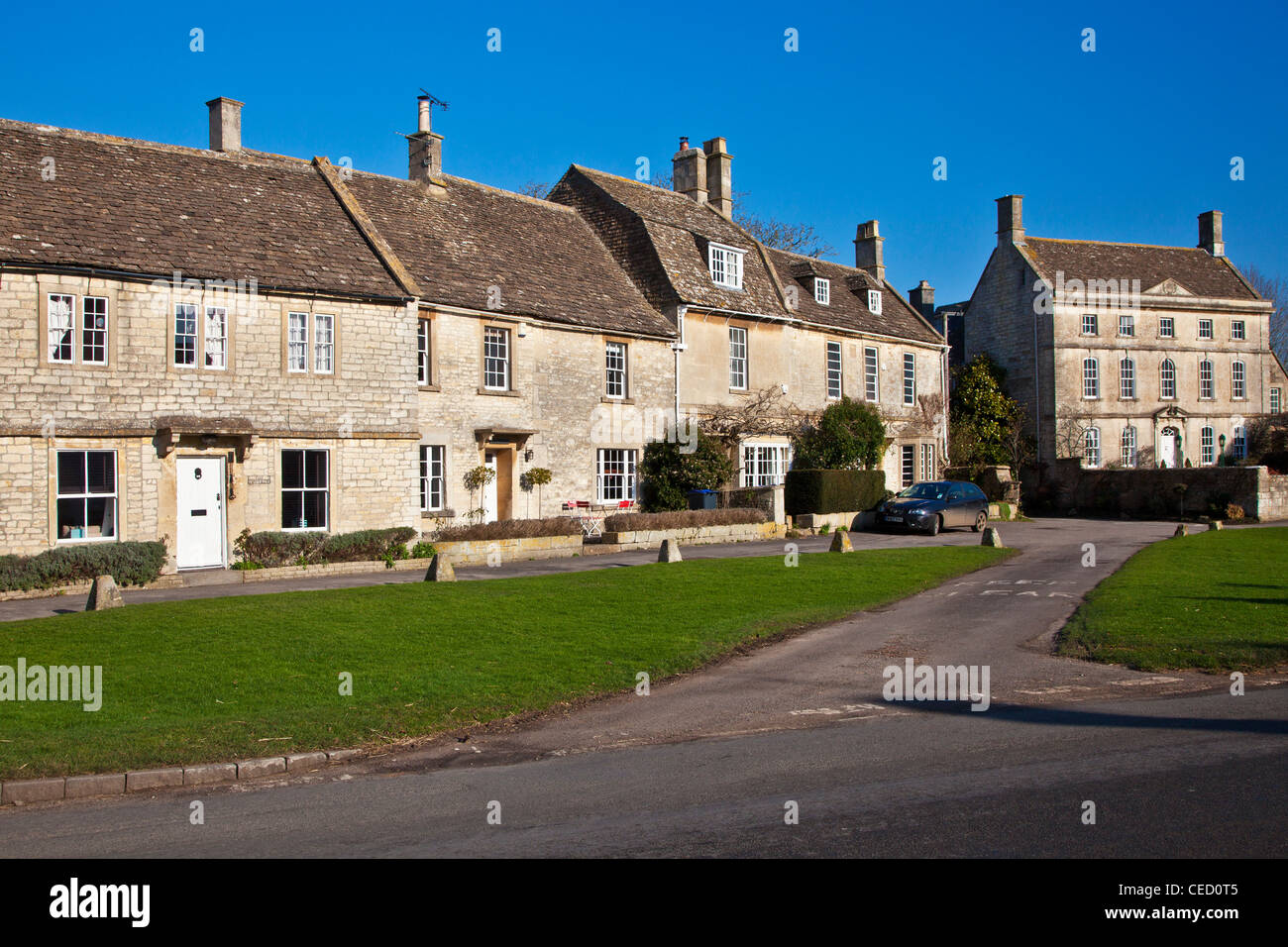 Cotswold stone houses and cottages around the green in the typical English country village of Biddestone, Wiltshire, - Stock Image