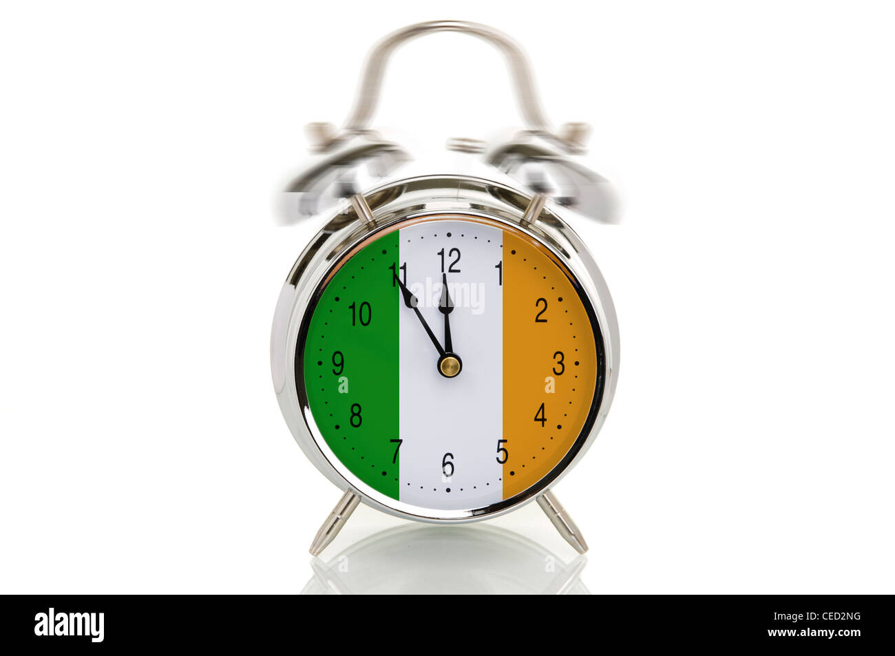 Ringing alarm clock with the Irish national flag, time set to five minutes to twelve, symbolic image for the crisis - Stock Image