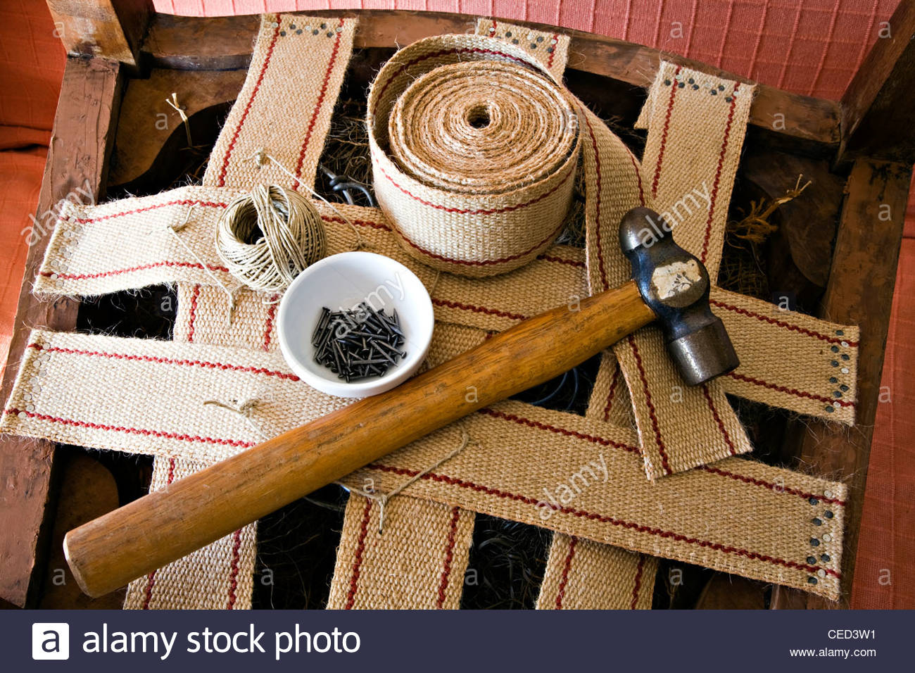 upholstery repair with jute webbing, nails, string and hammer - Stock Image