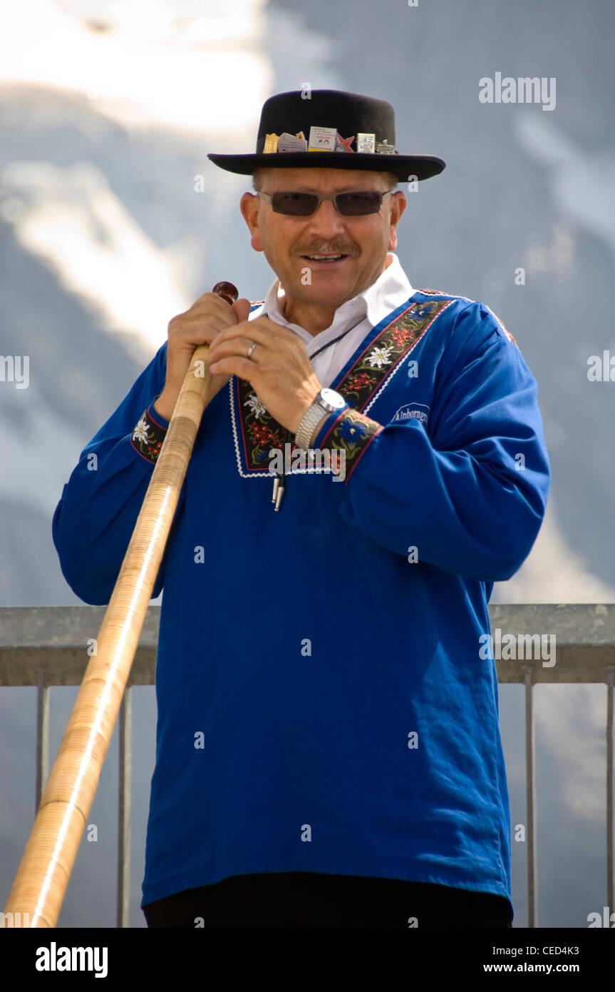 Vertical close up portrait of a traditionally dressed Swiss man holding an Alpine horn on a sunny day. - Stock Image