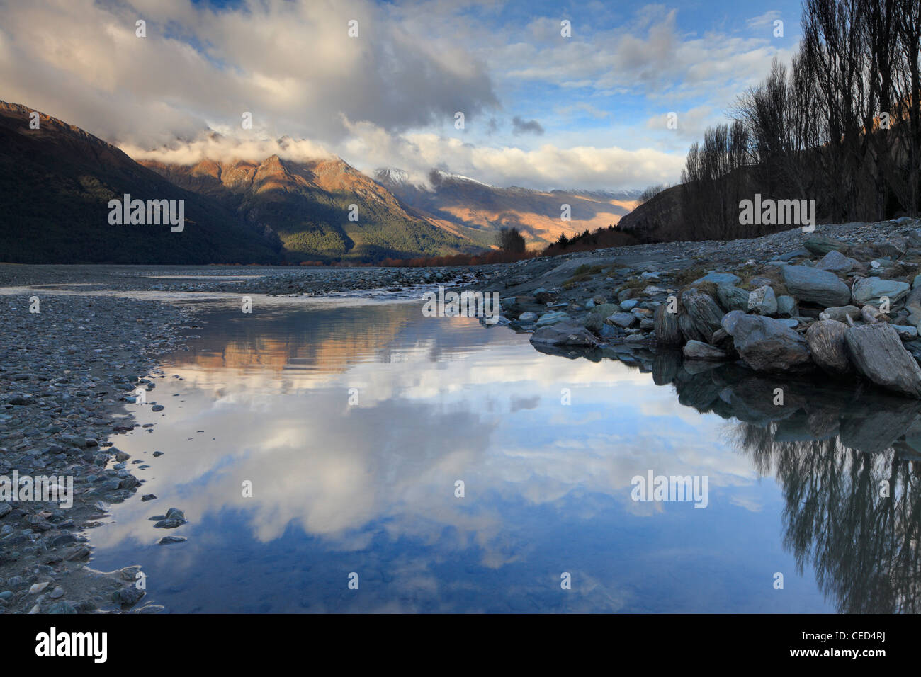 Snow-covered mountains reflected in an eddy of the Matukituki River in Mt Aspiring National Park - Stock Image