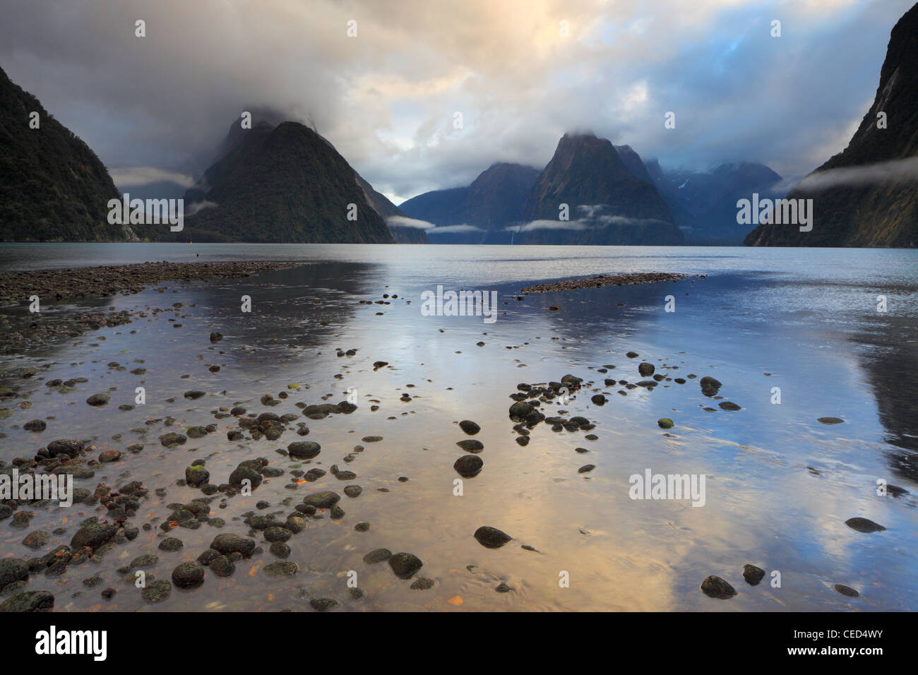 Sunrise over a misty Milford Sound in winter - Stock Image
