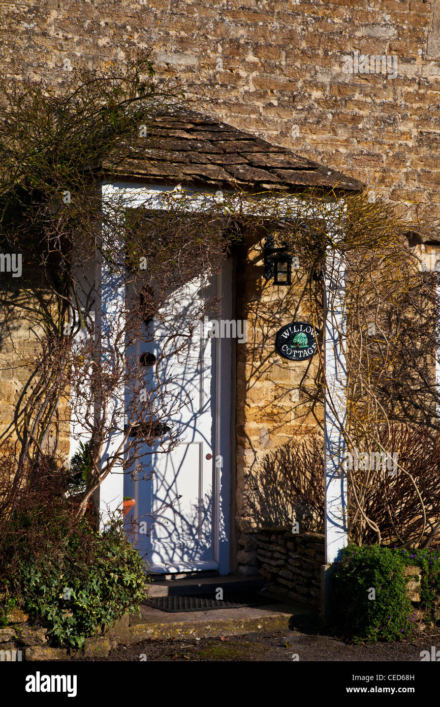 Gabled porch and white fornt door of a typical Cotswold stone cottage in winter. - Stock Image