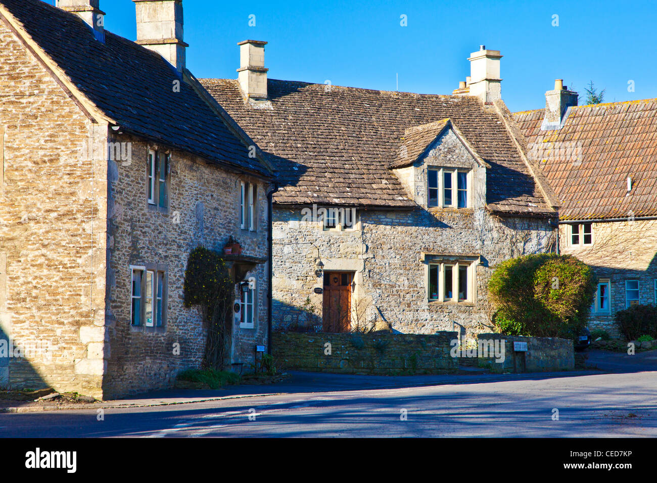 Typical Cotswold stone houses along the road through the English village of Biddestone, Wiltshire, England, UK - Stock Image