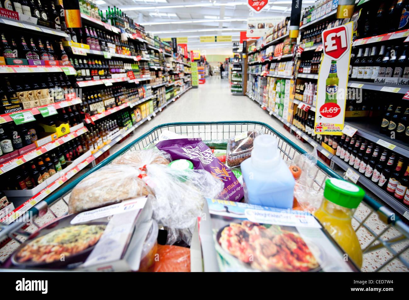 Tesco supermarket aisle and trolley, London, England, UK - Stock Image