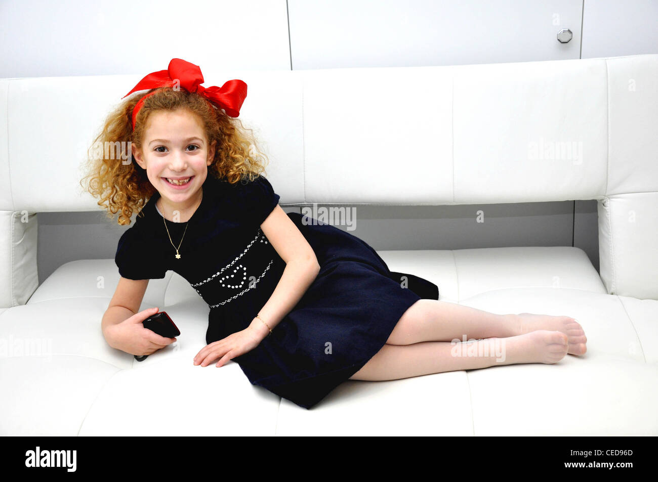Girl with a red bow smiling curly cute - Stock Image
