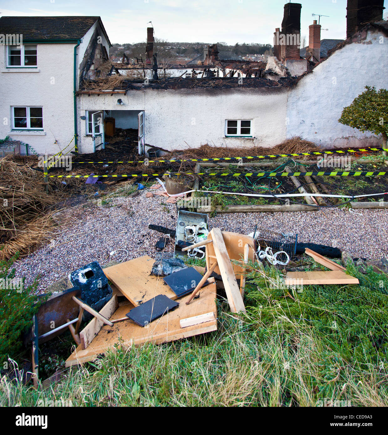 Remains of gutted thatched cottages after a fire in one of them spread to the rest destroying them, Crediton, Devon, - Stock Image