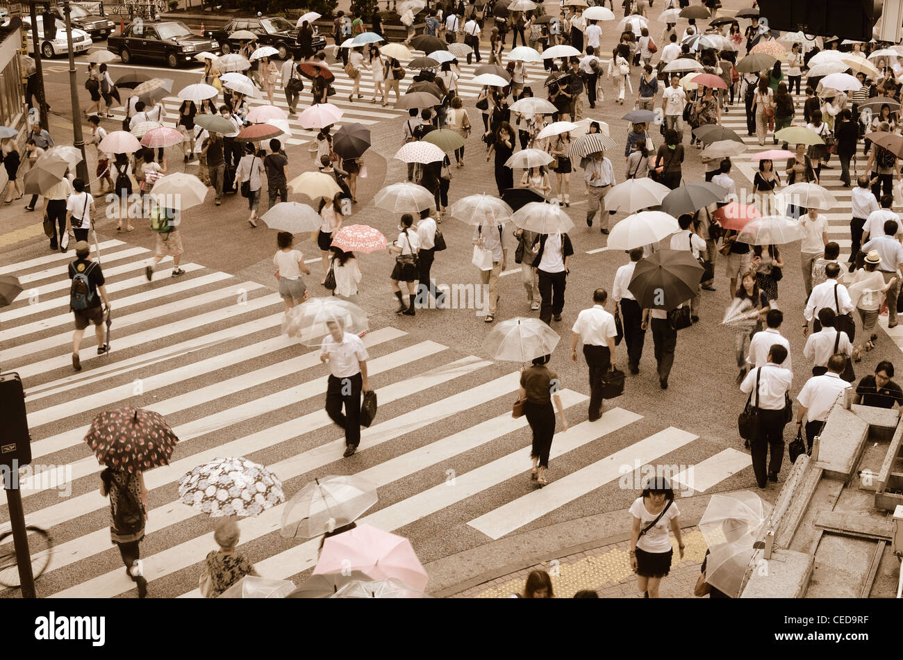 Pedestrians cross at Shibuya Crossing in Tokyo, Japan, the world's busiest crossing. - Stock Image