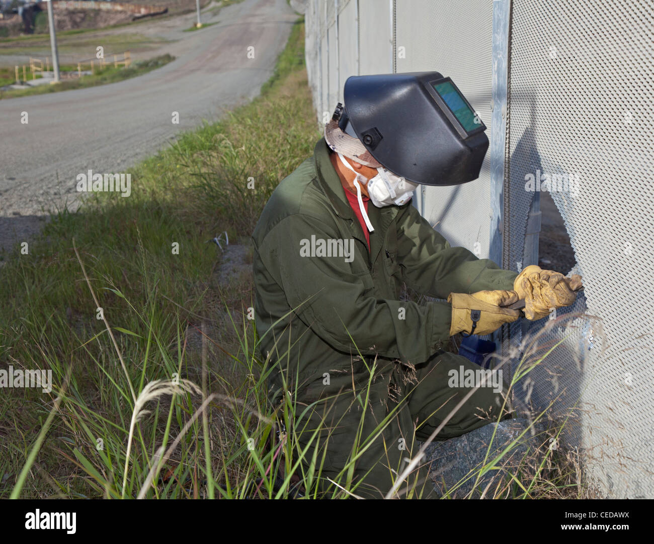 Worker Patches Hole Cut in U.S.-Mexico Border Fence Stock Photo