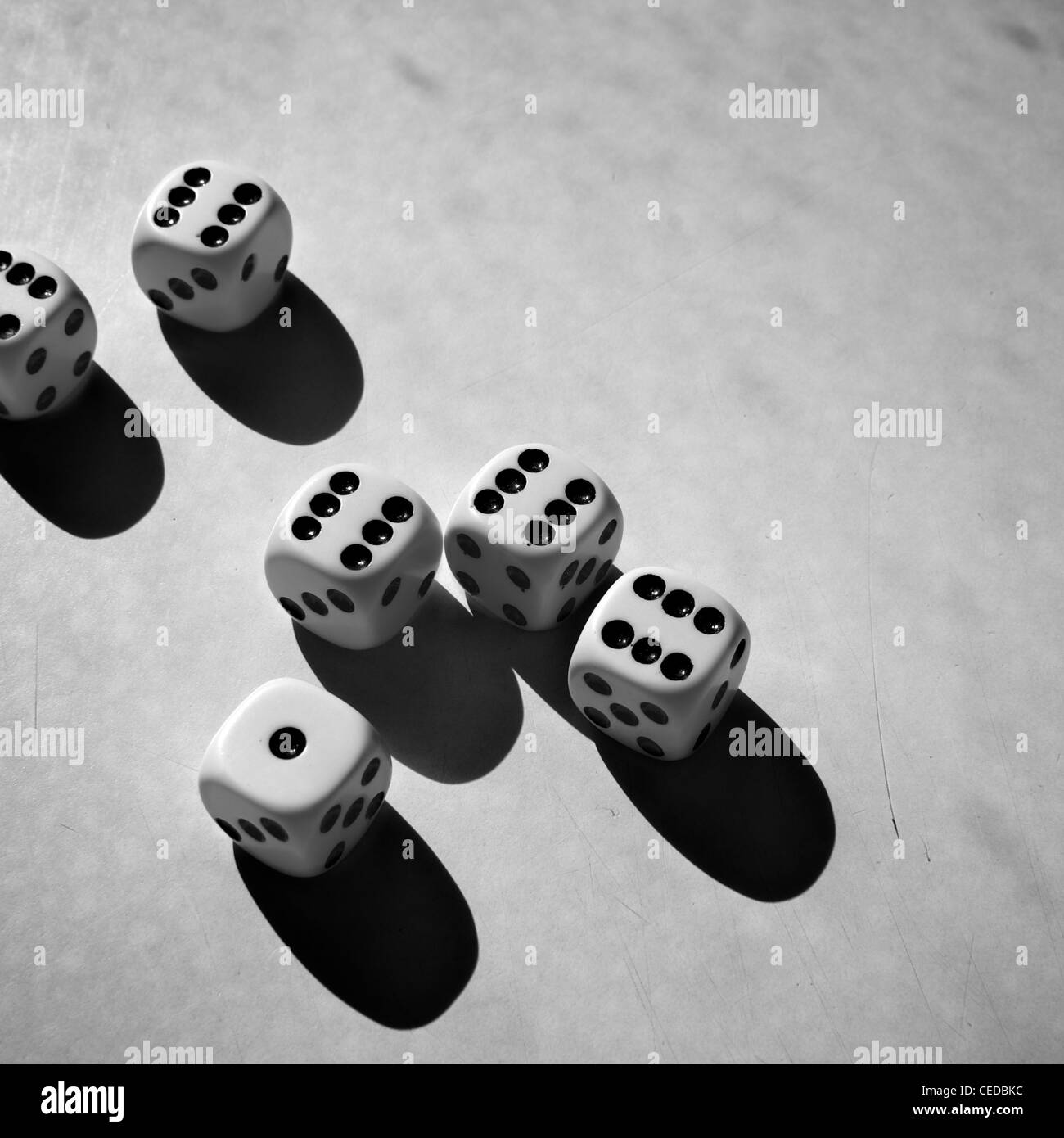 Six dices on a grungy scratched background surface. - Stock Image