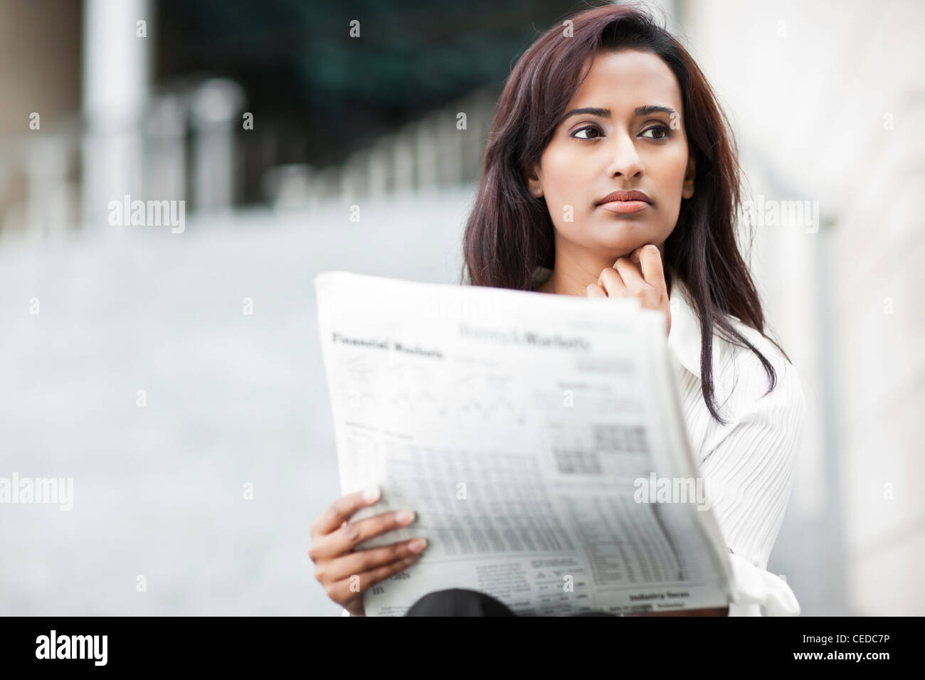 Indian businesswoman reading newspaper outdoors Stock Photo