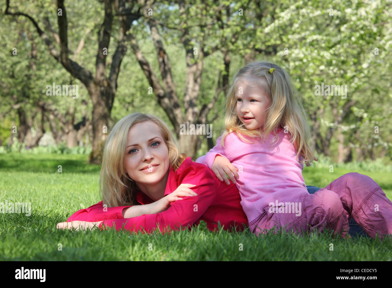 daughter has leant elbows on mother lying on grass in park - Stock Image