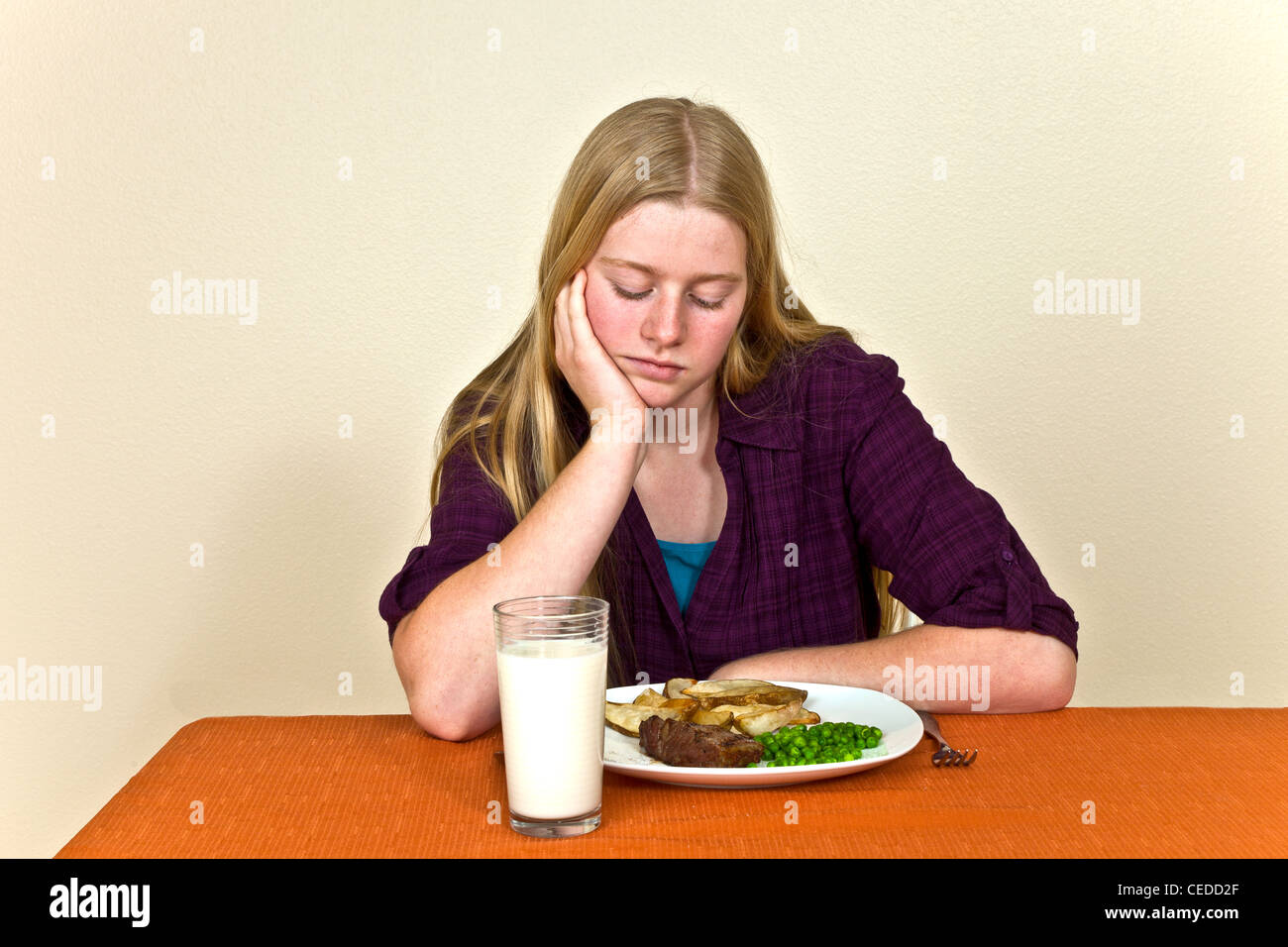 Strong willed stubborn Unhappy Young Caucasian 14-15 year old Teenage girl Sitting at table unhealthy attitude towards - Stock Image