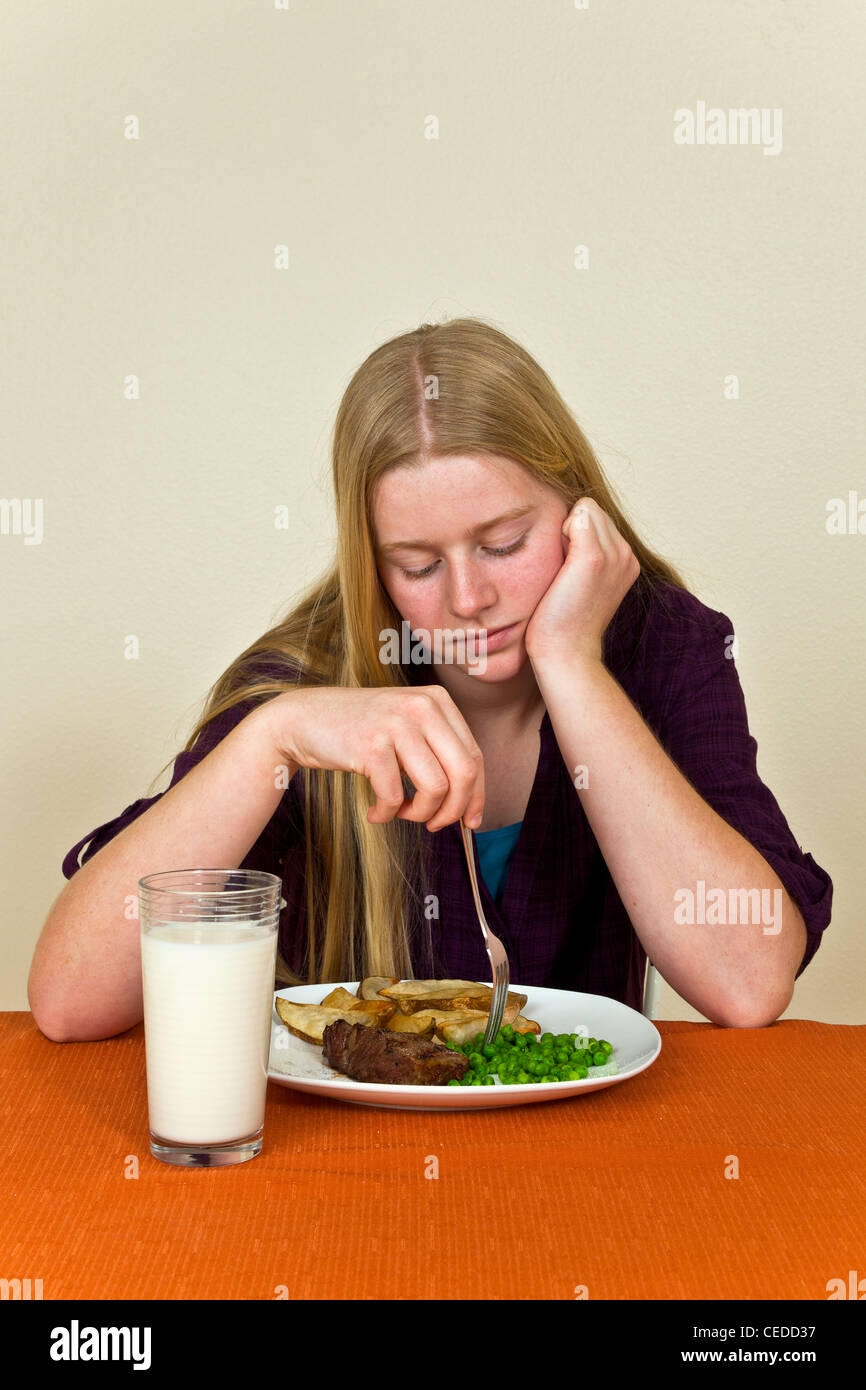 California Strong willed stubborn moping moody Teen girl at table Young Caucasian 13-16 year old olds dislikes playing - Stock Image