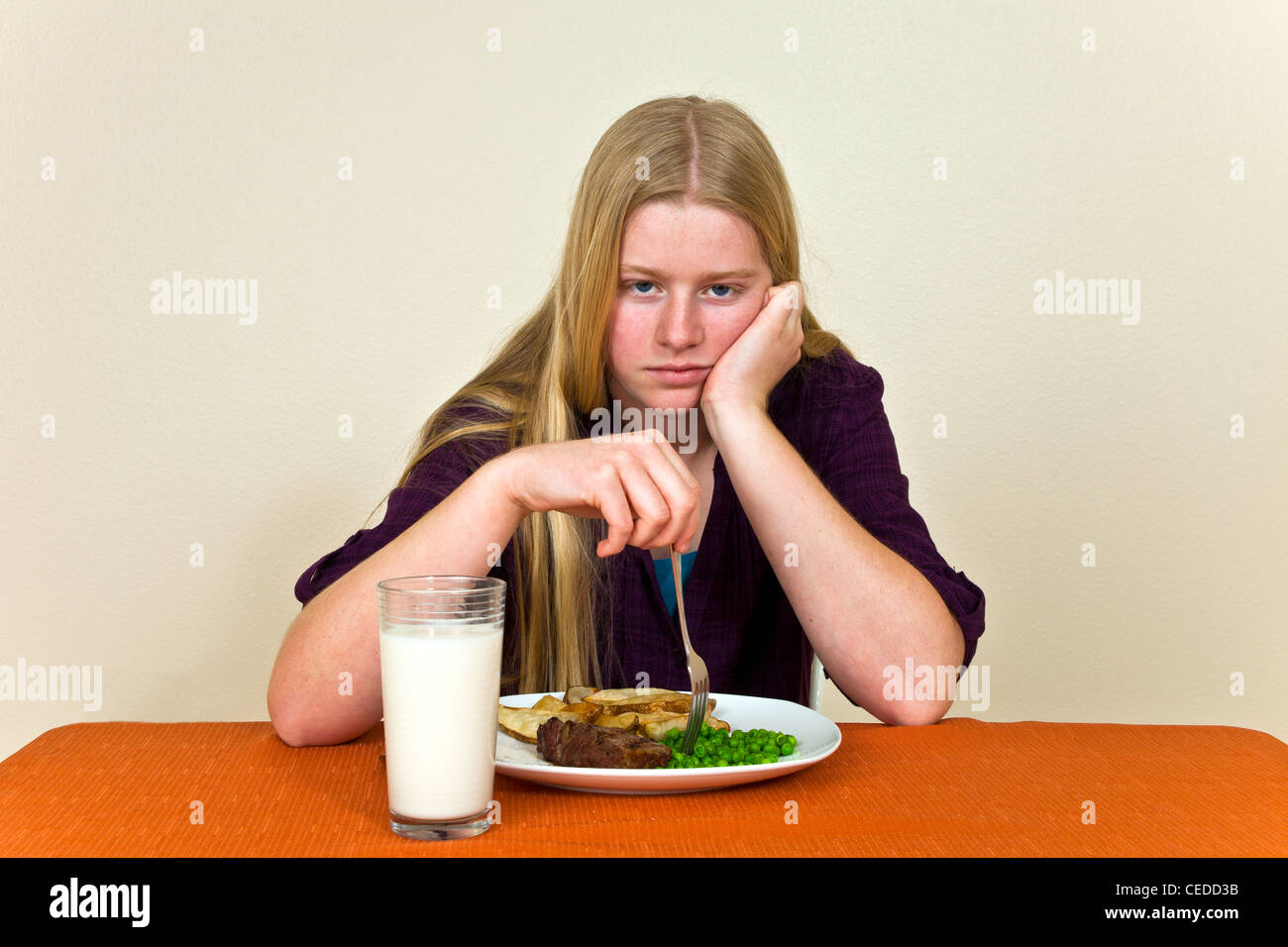Strong willed stubborn Teenage girl Sitting at table unhealthy attitude towards food dislikes won't eat her - Stock Image