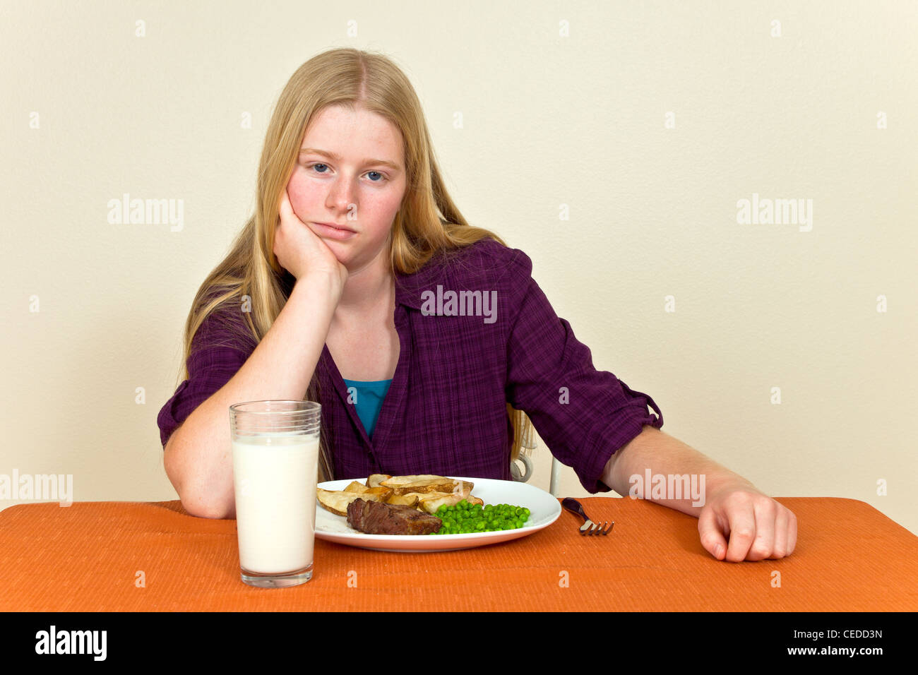 Strong willed stubborn Unhappy Teenage girl Sitting table unhealthy attitude towards food dislikes won't eat - Stock Image