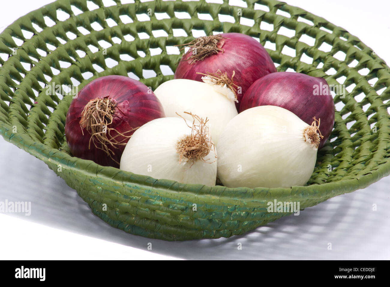 White and red onions in a basket on white background - Stock Image