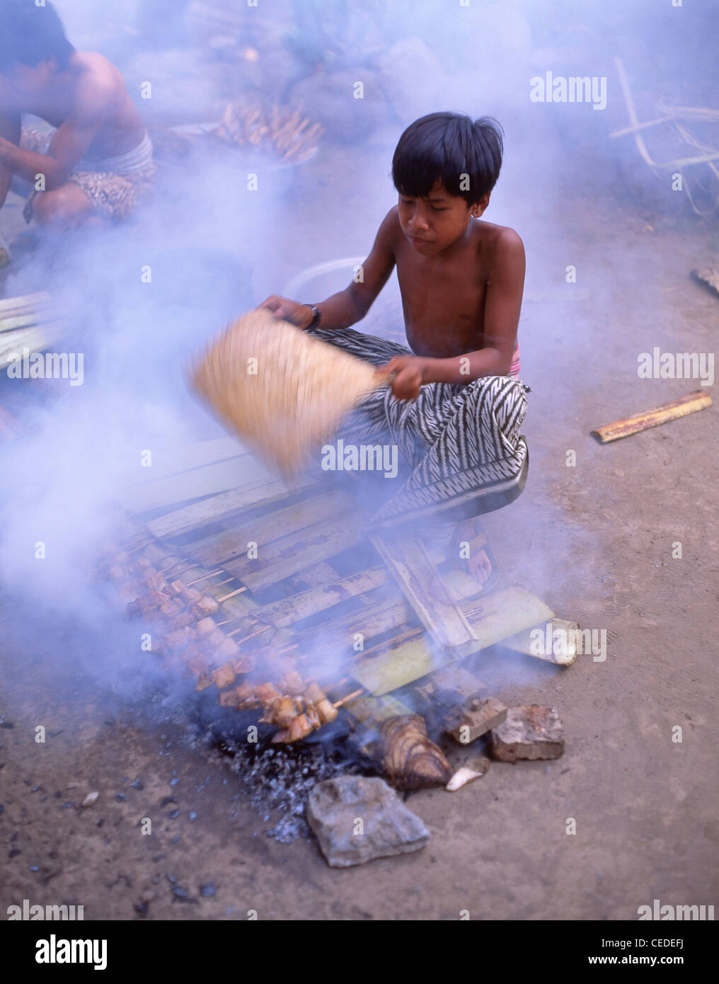 Young village boy cooking food on fire, Bali, Bali Province, Lesser Sunda Islands, Indonesia - Stock Image