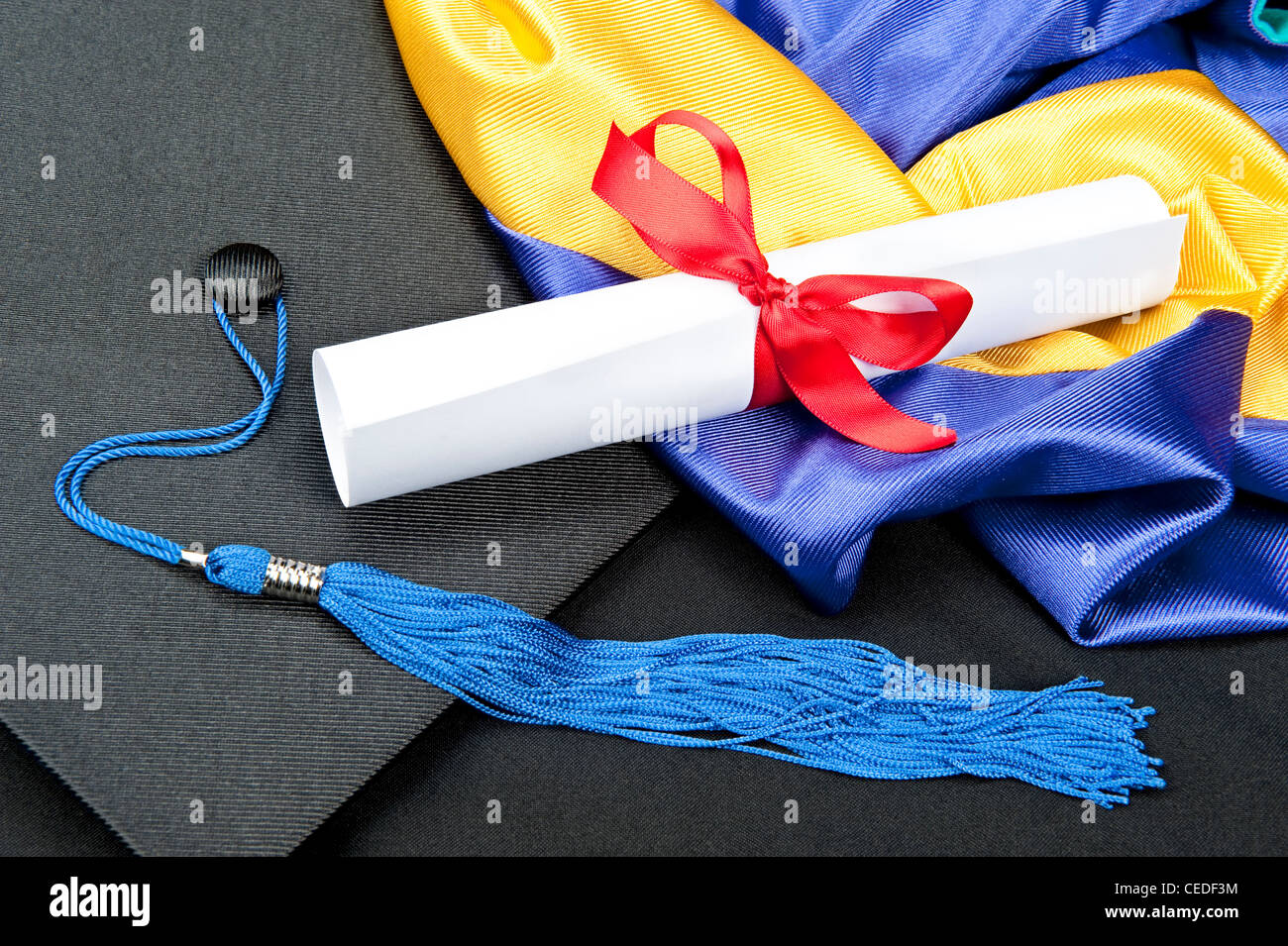 A graduation setting with cap,tassel, gown, hood and diploma. - Stock Image