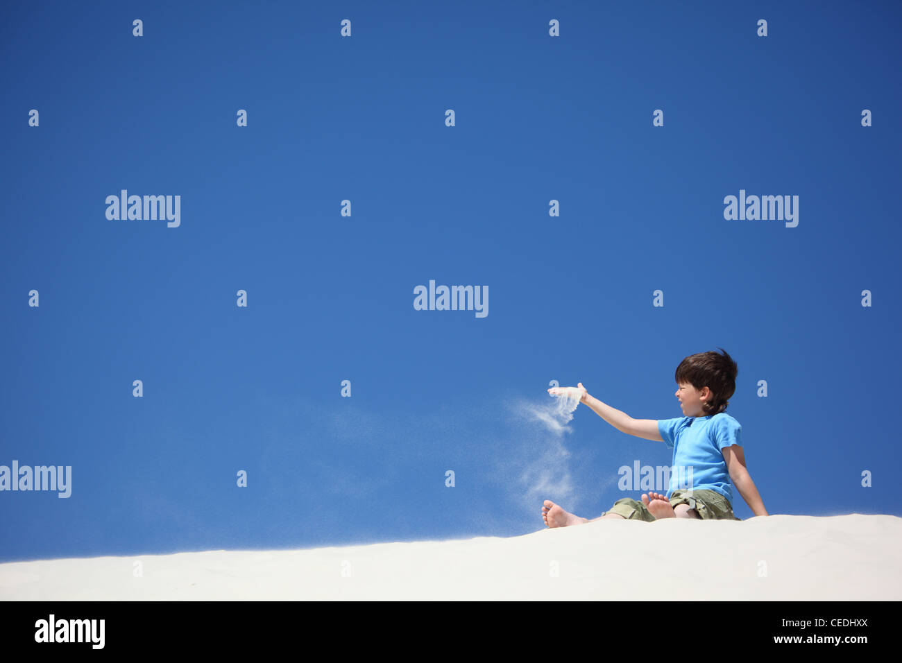 boy sits on sand and scatters it - Stock Image