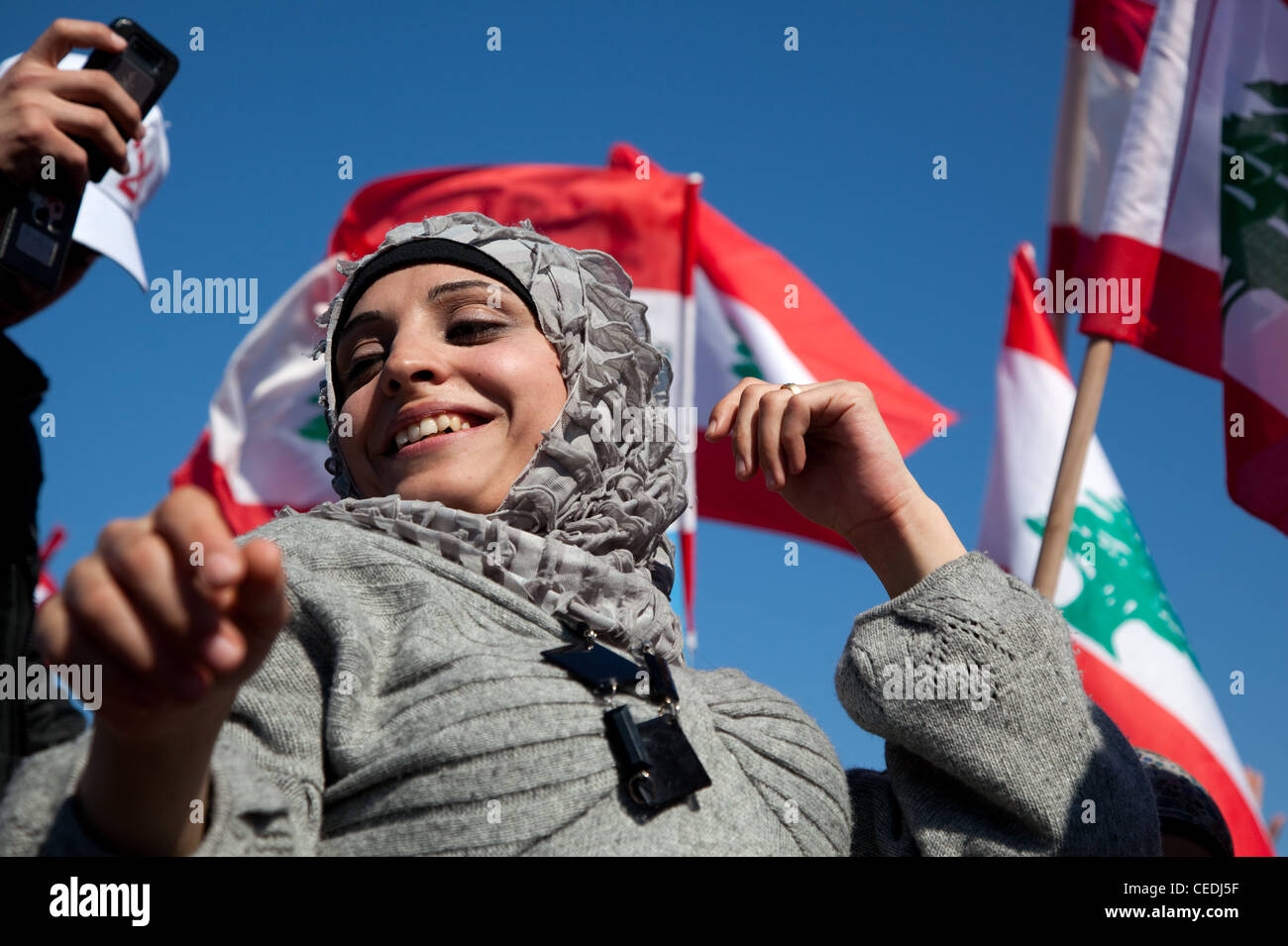 Young woman in stylish headscarf smiles and dances in close-up at a political rally in Martyrs Square, Beirut, Lebanon. - Stock Image