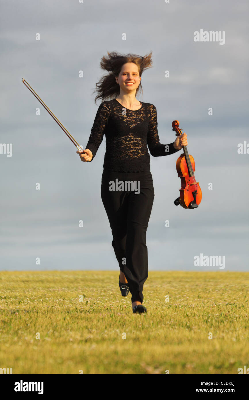 girl with violin runs on grass against  sky, front view Stock Photo