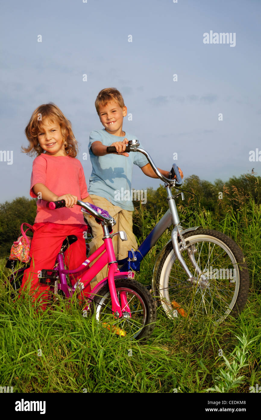 young smiling bikers rest outdoors - Stock Image