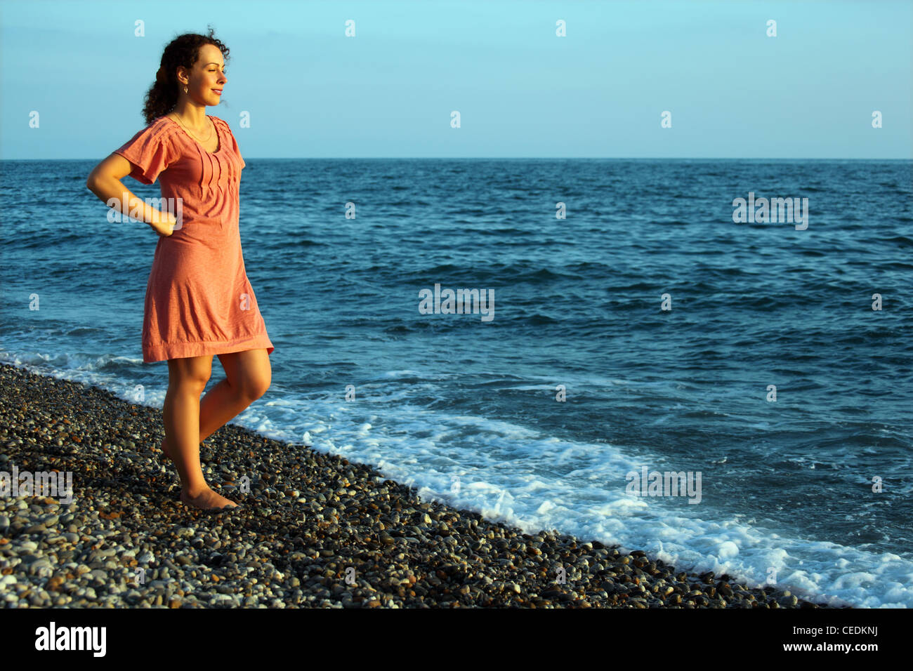 young woman stands ashore of sea - Stock Image