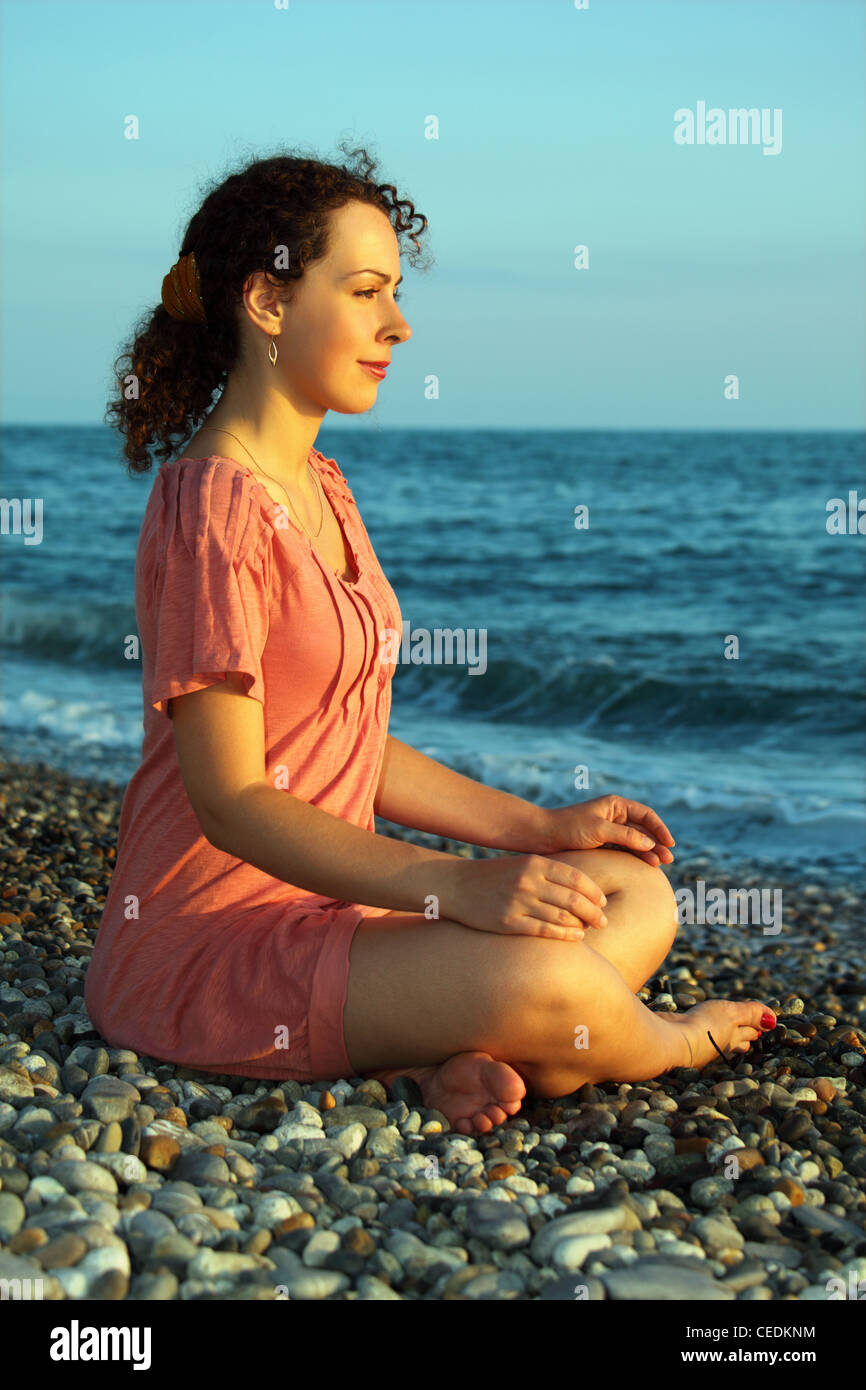 young woman sits and meditation ashore of sea - Stock Image