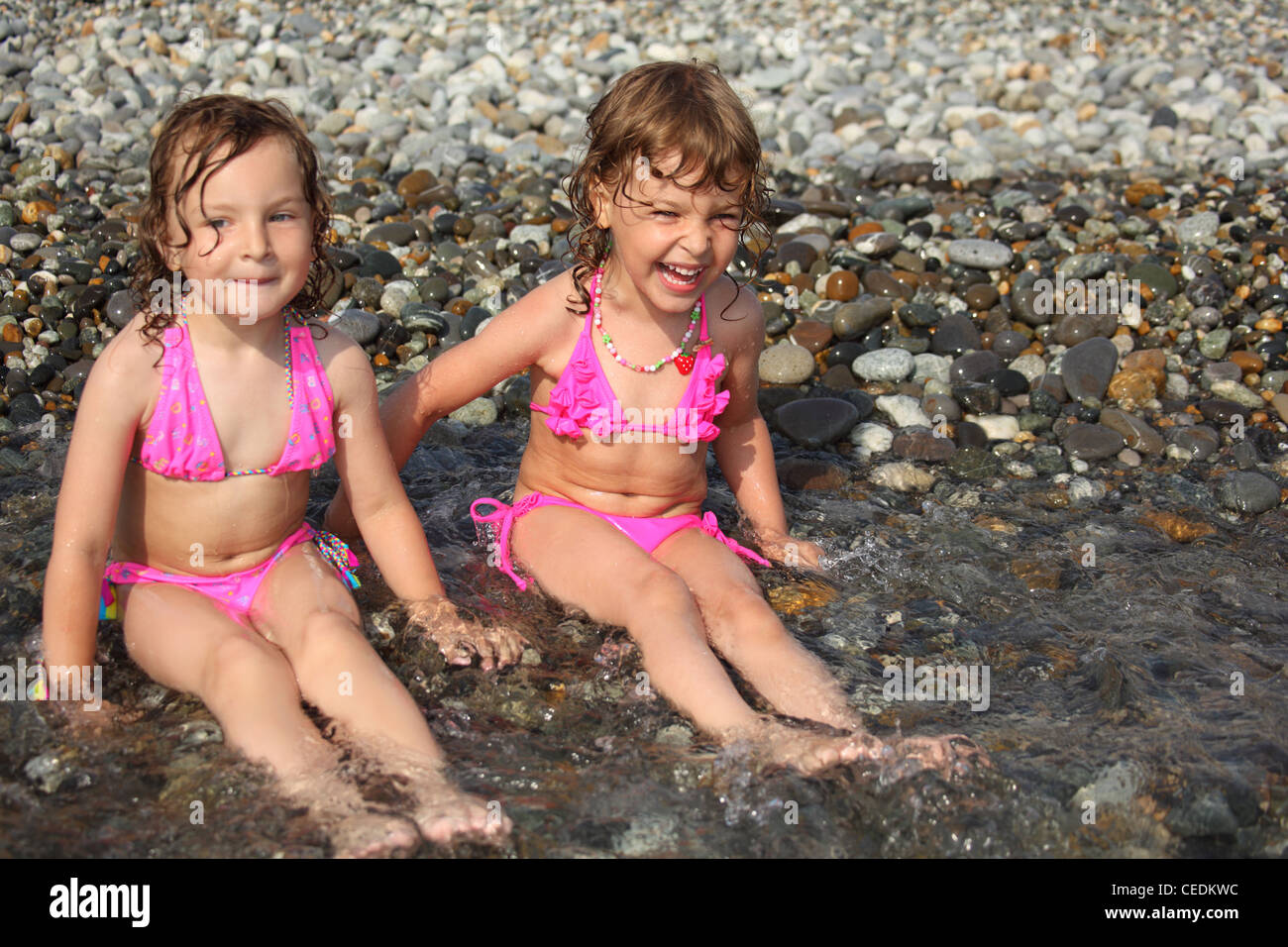 two little girls sit ashore in water - Stock Image