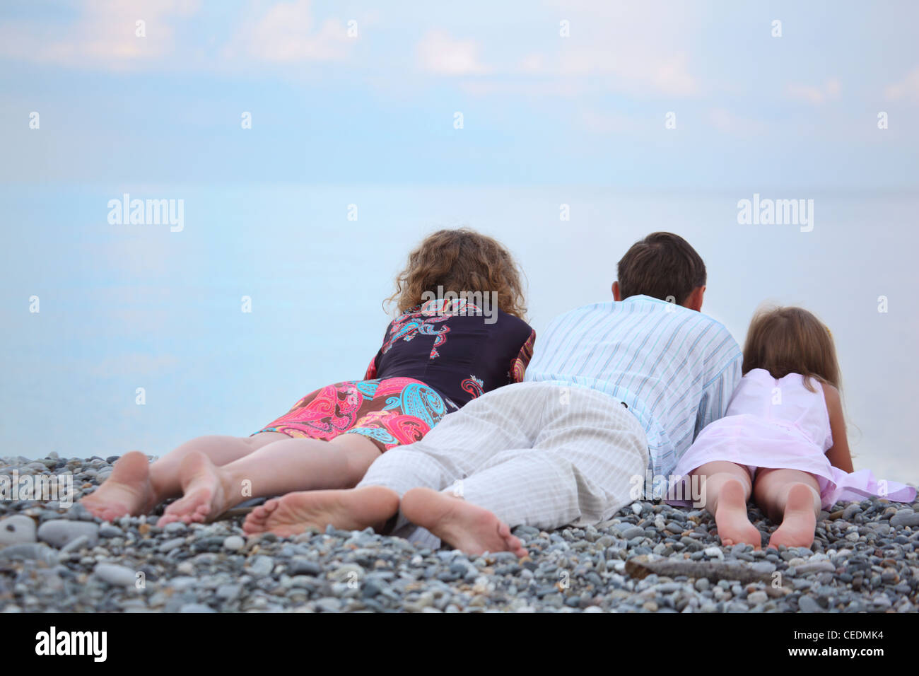 Happy family with little girl lying on stony beach, lying back - Stock Image