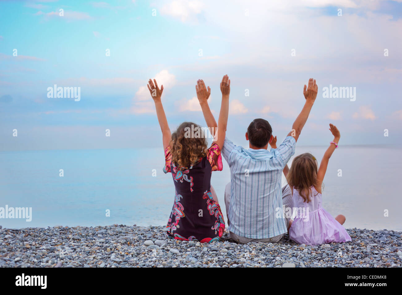 Happy family with little girl sitting on stony beach lifted hands upwards, sitting by back - Stock Image