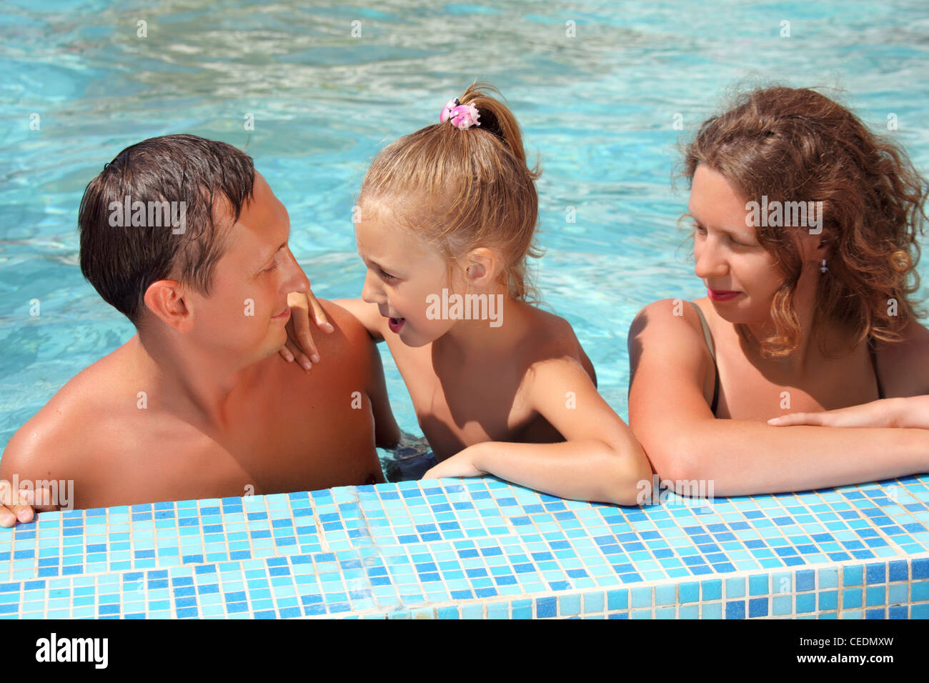 Happy family with little girl bathe in pool - Stock Image