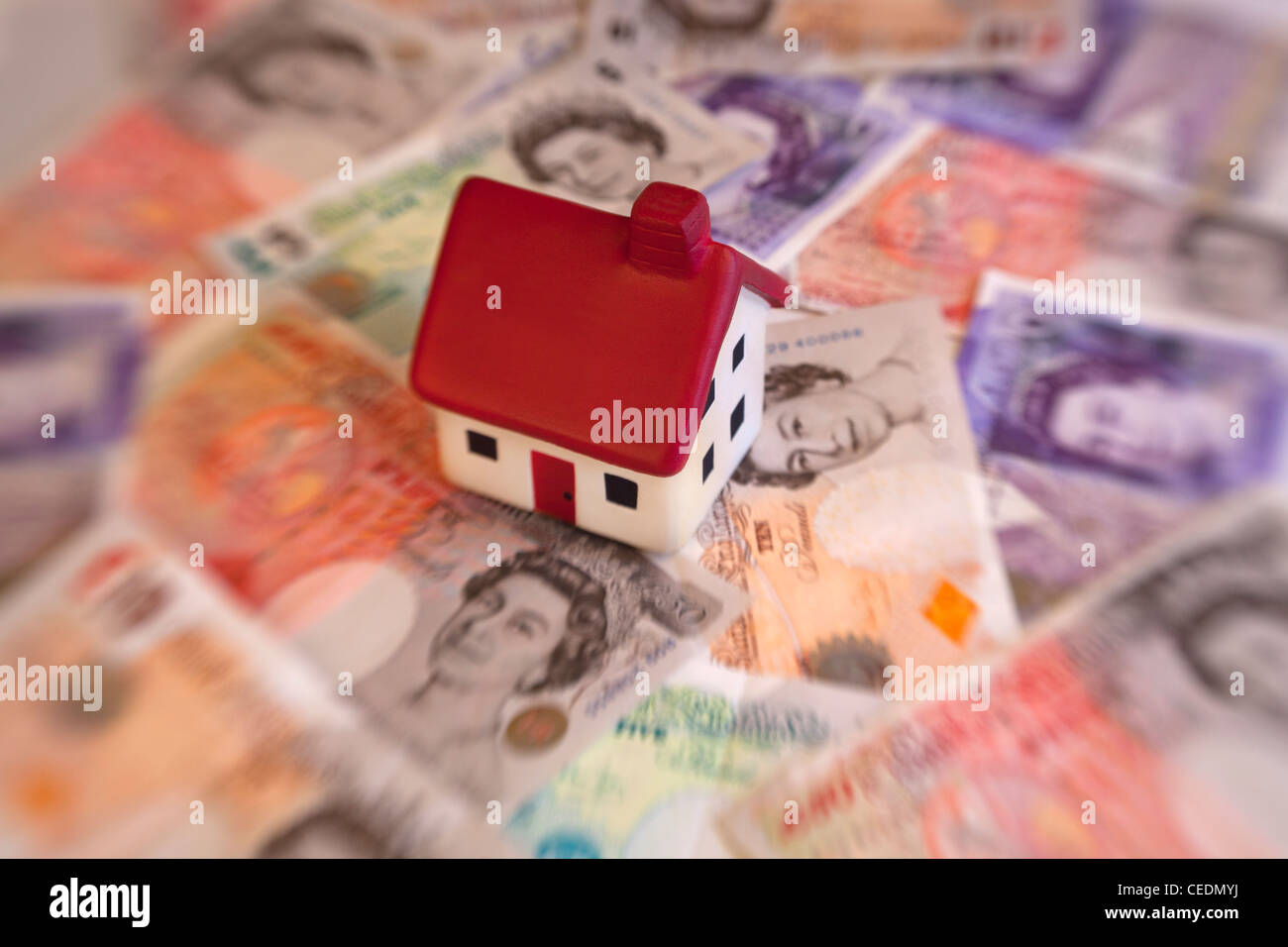 House on top of English pound note currency money - Stock Image