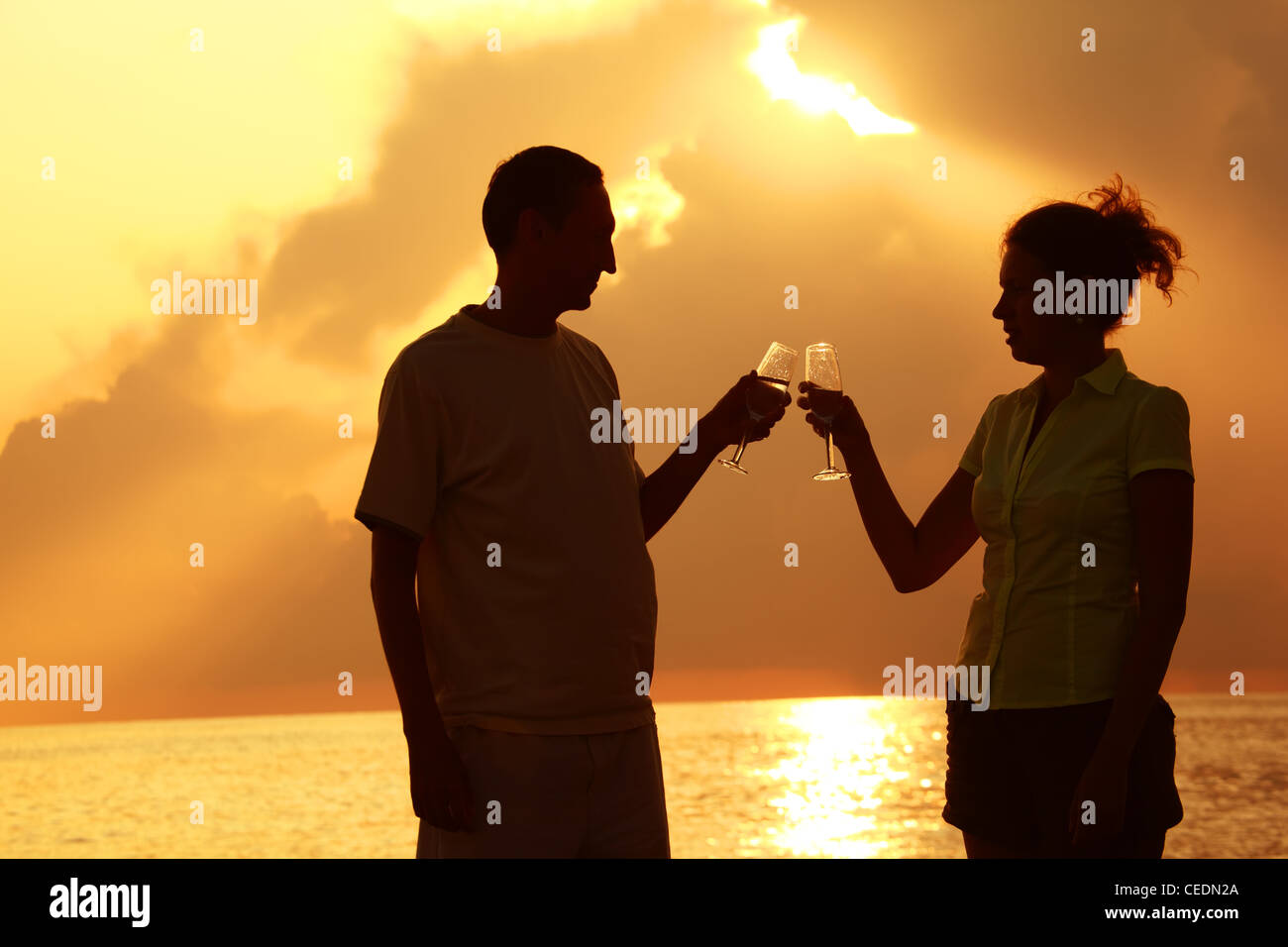 Man and woman clink glasses. Silhouettes against sea. - Stock Image
