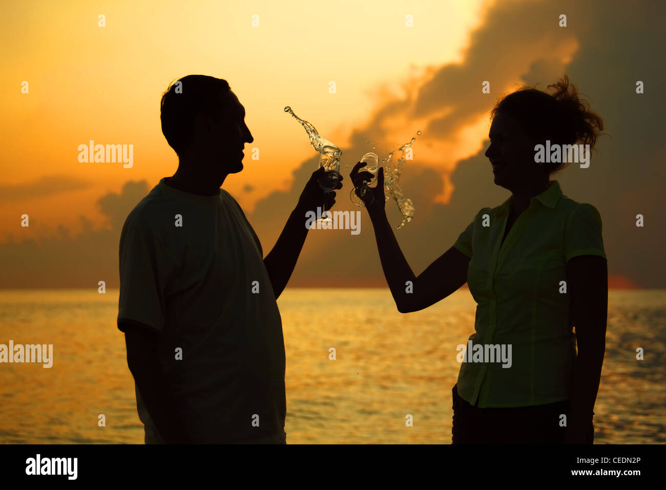 Man and woman clink glasses. Splashes of wine from glasses. Silhouettes against sea. - Stock Image