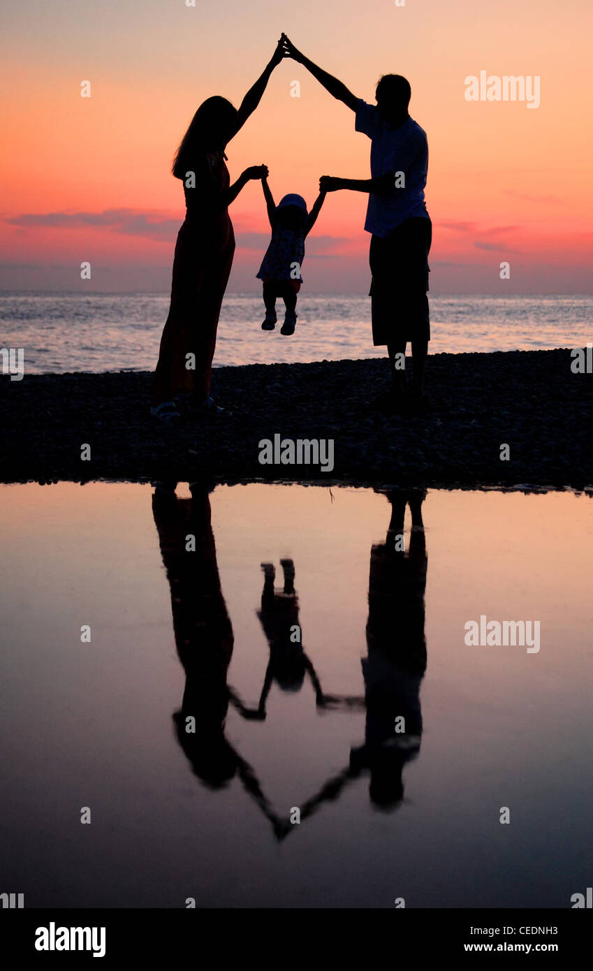 Silhouettes of parents with child against  sea decline - Stock Image