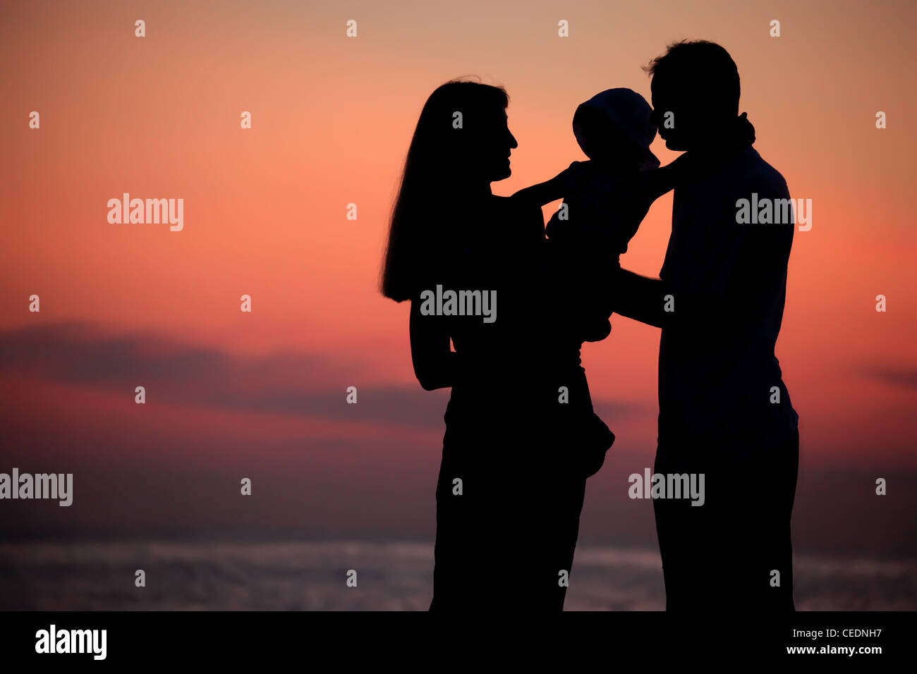 Silhouettes of parents with child on hands against  sea decline - Stock Image