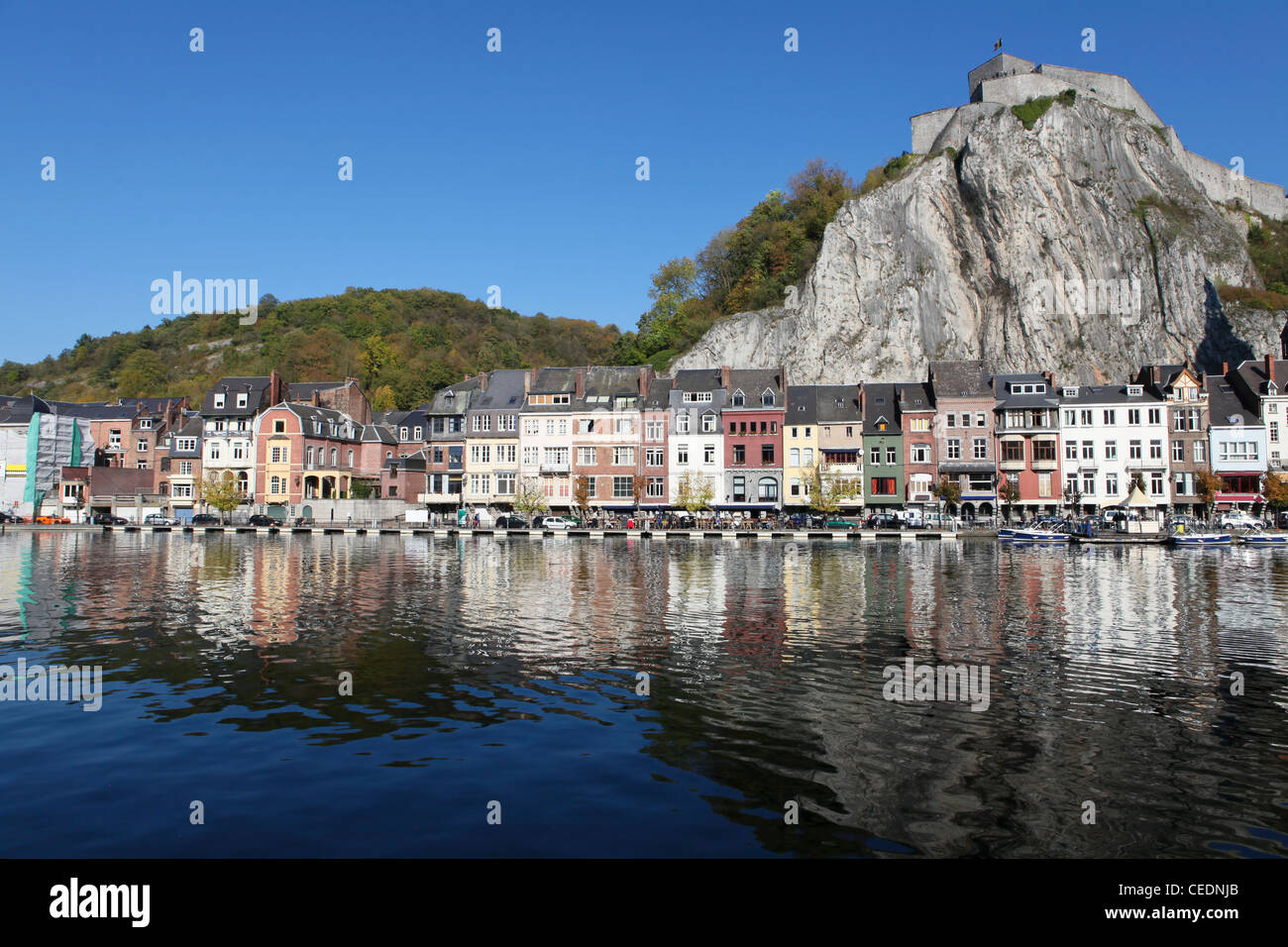 Citadelle and houses at the shore of the Meuse river in Dinant, Wallonia, Belgium. - Stock Image
